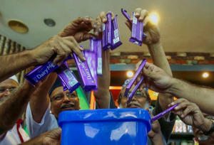 Members of Malaysian Muslim Wholesalers and Retailers Association (MAWAR), a non-governmental organization, throw Cadbury chocolate products into a dustbin as a protest and officially announced their boycott of Cadbury products, after their news conference on stopping the supply of Cadbury chocolate products to retail shops, in Kuala Lumpur May 29, 2014.
