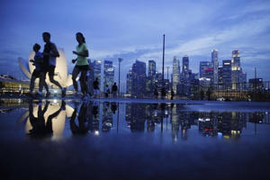 Joggers run past as the skyline of Singapore's financial district is seen in the background April 21, 2014.