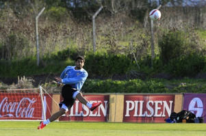 Uruguay's National soccer team striker Luis Suarez kicks the ball during a team practice at the team's headquarters in the outskirts of Montevideo, September 2, 2013.