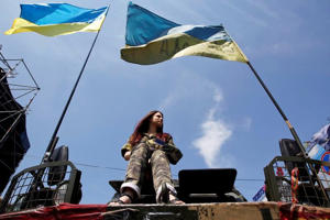A woman sits on an armoured personnel vehicle during a rally demanding official information from the Ukrainian government on their work in the 100 days since they took power, at Independence Square in Kiev June 8, 2014.: A woman sits on an armoured personnel vehicle during a rally at Independence Square in Kiev