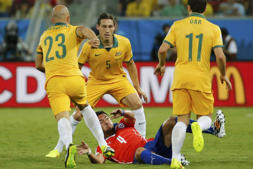 Chile's Mauricio Isla falls under pressure from the Socceroos.