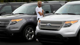 Man looking at Ford explorer: US car giant Ford recalls a total of 1.4 million vehicles, the majority of which are sport utility vehicles sold in North America that could suffer a loss of power steering.