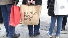 Shoppers in New York waiting to cross the sidewalk clutching their shopping bags
