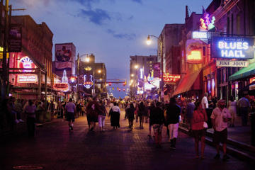 Pedestrians walk down Beale Street at dusk in downtown Memphis, Tennessee. For the first time in nine years, the U.S. economy is expected to contribute more to global GDP than China in 2015.