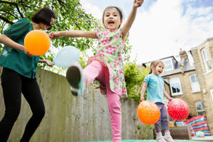 Mother and daughters playing in garden with balloons