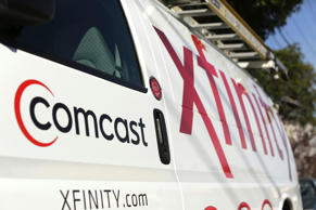 A Comcast sign is shown on the side of a vehicle in San Francisco, California in this file photo taken February 13, 2014. Comcast Corp, the largest U.S. cable operator, posted higher first-quarter revenue and net income on Tuesday showing it could add video subscribers for two quarters in a row, a rare sight in the cable industry. REUTERS/Robert Galbraith/Files (UNITED STATES - Tags: BUSINESS)