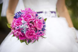 Bride holding bright pink and purple wedding bouquet in her hand