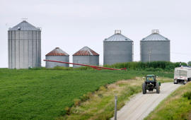 File photo a farmer drives his tractor past a soybean field toward grain storage bins near Ladora, Iowa.