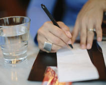 Woman signing check at restaurant