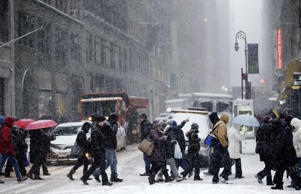 Pedestrians walk through heavy snow in the midtown section of New York, Monday, Jan. 26, 2015.