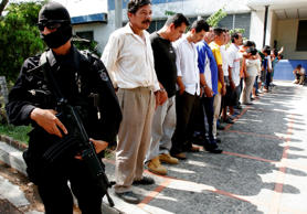 A police officer stands guard as alleged gang members are shown to the media in San Salvador.