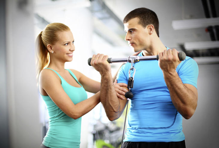 Woman at gym touches a guy's biceps during his workout.