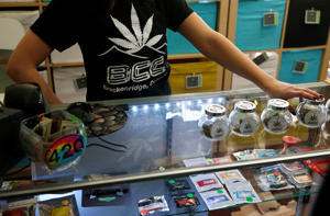 In this Dec. 11, 2014 photo, a pot store employee talks with customers inside the Breckenridge Cannabis Club, which sells recreational marijuana products, in the ski town of Breckenridge, Colo.