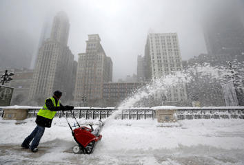 A worker pushes a snow plough to clear a path during blizzard conditions in Chicago, Illinois, February 1, 2015.     Jim Young/Reuters