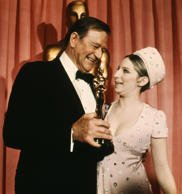"Hollywood, UNITED STATES: In this 1969 photo, US actor John Wayne accepts his Best Actor Oscar from US singer and actress Barbara Streisand. Wayne won for his role in ""True Grit."" The 100th anniversary of Wayne's birth is being observed 26 May 2007. Wayne was born Marion Robert Morrison in Winterset, Iowa. His career began in silent movies in the 1920s and was a major star from the 1940s to the 1970s. He died 11 June 1979. AFP PHOTO (Photo credit should read STAFF/AFP/Getty Images)"