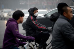 A man wearing a mask rides his bicycle along a street in Beijing.