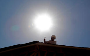 In this July 25, 2014 file photo, a roofer works under the mid-day sun in Gilbert, Ariz. Federal science officials announced Friday that for the third time in a decade, the globe sizzled to the hottest year on record. Both the National Oceanic and Atmospheric Administration and NASA calculated that in 2014 the world had its hottest year in 135 years of record-keeping.