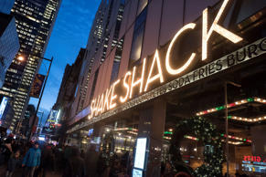 People walk in front of the Shake Shack restaurant in the Manhattan borough of New York, December 29, 2014. Burger chain Shake Shack Inc, which grew out of a hot dog stand in New York's Madison Square Park, has filed for an initial public offering at a time when stock offerings by casual restaurants have proven to be a big hit with investors. REUTERS/Keith Bedford (UNITED STATES - Tags: BUSINESS FOOD)
