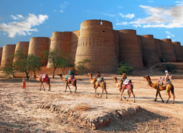 A caravan of camels passes by Derawar Fort, Cholistan Desert in the afternoon.