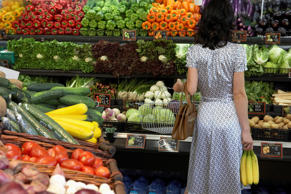 Woman buying produce at supermarket.