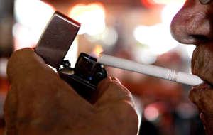 In this June 11, 2009 file photo, a customer at the Red Key Taven in Indianapolis lights a cigarette.