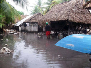 In this handout image provided by Plan International Australia, a man stands in flood waters on March 13, 2015, on the island of Kiribati. Cyclone Pam is pounding South Pacific islands with hurricane force winds, huge ocean swells and flash flooding.  Plan International Australia/Getty Images