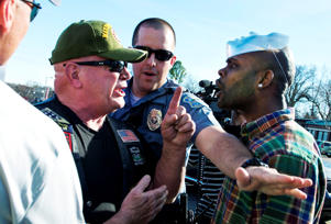 A Ferguson police officer tries to separate a supporter of Michael Brown (R) from a Ferguson police supporter, outside the Ferguson Police Department and Municipal Court in Ferguson, Missouri, March 15, 2015. News of Sunday's arrest of suspect Jeffrey Williams in last week's shooting of two policemen during a protest rally in Ferguson, prompted a show of support for Ferguson's beleaguered police force. Williams, 20, has admitted to firing the shots that wounded the officers early on Thursday, said St. Louis County Prosecuting Attorney Robert McCulloch, and told investigators that he was not targeting police but was shooting at someone else.