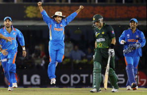 India's Sachin Tendulkar, second left, MS Dhoni, right, and Yuvraj Singh, left, celebrate their win by 29 runs as Pakistan batman Misbah ul-Haq walk away during the Cricket World Cup semifinal match between India and Pakistan in Mohali, India, Wednesday, March 30, 2011.