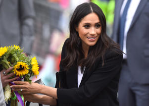 Britain's Meghan, the Duchess of Sussex, accepts some flowers during a visit to Parliament Square in Trinity College, Dublin, Ireland, July 11, 2018. REUTERS/Cathal McNaughton
