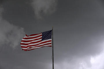 Storm clouds loom over an American flag in Convent, Louisiana, U.S., June 11, 2018. Picture taken June 11, 2018. REUTERS/Jonathan Bachman