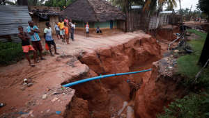 Residents look at a road that collapsed in the aftermath of Cyclone Kenneth, at Wimbe village in Pemba, Mozambique, April 29, 2019.