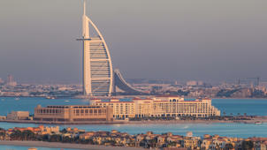 Dubai skyline with villas nad Burj Al Arab during sunset timelapse.  Top view from atlantis on palm jumeirah.