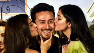 Indian Bollywood actresses Tara Sutaria (L) and Ananya Pandey (R) kiss on the cheeks of actor Tiger Shroff (C) as they pose for photographs during the trailer launch of their upcoming romantic comedy drama Hindi film 'Student of the Year 2' in Mumbai on April 12, 2019. (Photo by Sujit Jaiswal / AFP)        (Photo credit should read SUJIT JAISWAL/AFP/Getty Images)