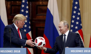 U.S. President Donald Trump receives a football from Russian President Vladimir Putin as they hold a joint news conference after their meeting in Helsinki, Finland July 16, 2018.
