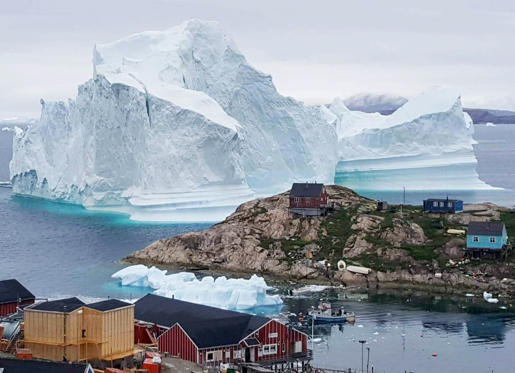 Slide 1 of 33: A picture taken on July 13, 2018 shows an iceberg behind houses and buildings after it grounded outside the village of Innarsuit, an island settlement in the Avannaata municipality in northwestern Greenland.