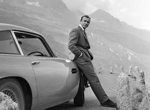 1964:  Actor Sean Connery poses as James Bond next to his Aston Martin DB5 in a scene from the United Artists film 'Goldfinger' in 1964.  (Photo by Donaldson Collection/Michael Ochs Archives/Getty Images)