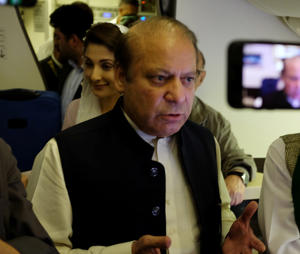 Ousted Pakistani Prime Minister Nawaz Sharif gestures as he boards a Lahore-bound flight due for departure, at Abu Dhabi International Airport, UAE July 13, 2018.
