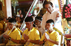 Coach Ekkapol Janthawong, center, and members of the rescued soccer team attend a Buddhist ceremony that is believed to extend the lives of its attendees as well as ridding them of dangers and misfortunes in Mae Sai district, Chiang Rai province, northern Thailand, Thursday, July 19, 2018. The 12 boys and their soccer coach rescued from a cave in northern Thailand left the hospital where they had been recuperating and appeared at a news conference Wednesday, saying the ordeal made them stronger and taught them not to live carelessly. (AP Photo/Sakchai Lalit)