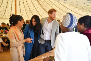 Meghan, Duchess of Sussex (C), her mother, Doria Ragland (L) and Prince Harry, Duke of Sussex take part in the launch of a cookbook with recipes from a group of women affected by the Grenfell Tower fire at Kensington Palace in London on Sept. 20, 2018.
