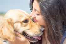 Close up picture of young pretty woman kissing her dog