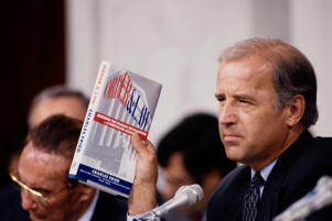"Senator Joseph Biden holds up the book ""Order and Law"" by Charles Fried during the 1991 Clarence Thomas hearings."