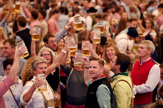 Slide 1 of 40: Visitors cheer during the opening day of the 185th Oktoberfest in Munich, Germany September 22, 2018. REUTERS/Andreas Gebert