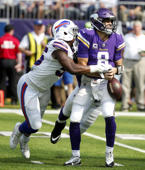 Minnesota Vikings quarterback Kirk Cousins fumbles as he is hit by Buffalo Bills defensive end Jerry Hughes, left, during the first half of an NFL football game, Sunday, Sept. 23, 2018, in Minneapolis.