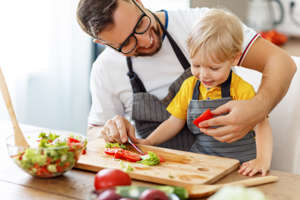 happy family father with son  preparing vegetable salad at home