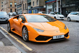 An orange coloured Lamborghini Huracan LP 610-4 sports car parked on a street in Glasgow, Scotland, UK.