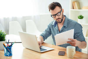Portrait of concentrated businessman in glasses with laptop reading contract