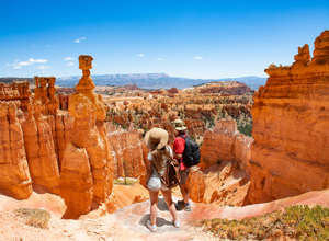 Couple on hiking trip looking at beautiful  mountain landscape.  Friends  relaxing on top of the mountain.  Bryce Canyon National Park, Utah, USA