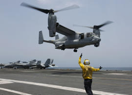 "In this Friday, May 17, 2019, photo released by the U.S. Navy, Aviation Boatswain's Mate 2nd Class Nicholas Hawkins, from Houston, Texas, signals an MV-22 Osprey to land on the flight deck of the Nimitz-class aircraft carrier USS Abraham Lincoln in the Arabian Sea. Commercial airliners flying over the Persian Gulf risk being targeted by ""miscalculation or misidentification"" from the Iranian military amid heightened tensions between the Islamic Republic and the U.S., American diplomats warned Saturday, May 18, 2019, even as both Washington and Tehran say they don't seek war. (Mass Communication Specialist 3rd Class Amber Smalley/U.S. Navy via AP)"