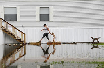 Samantha Karnes and her son Anthony Pickett, 3, walk up to their neighbor's mobile home to check on him as floodwater from the Arkansas River approaches at the Riverside Mobile Home Park in Muskogee, Okla., Wednesday, May 22, 2019.