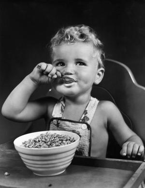 circa 1945:  A boy wearing overalls sits in a high chair and eats a bowl of rice puffed cereal with a spoon.  (Photo by Lambert/Getty Images)